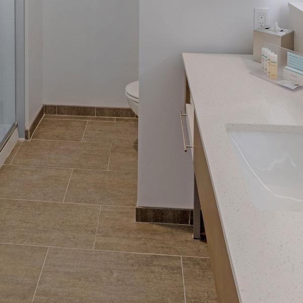 sandstone porcelain tile flooring in hotel bathroom
