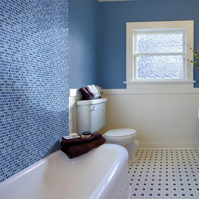 clean blue and white bathroom with glass tile tub surraound