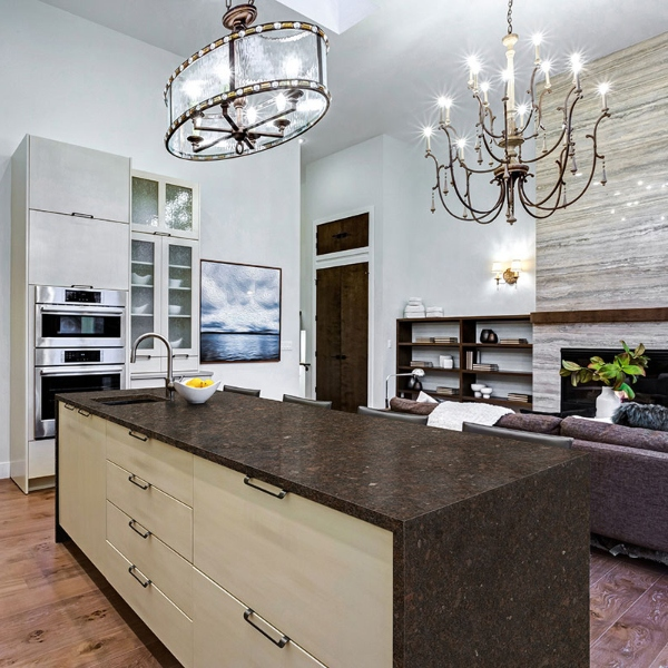 granite waterfall kitchen with chandelier