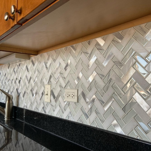 black granite kitchen counter with herringbone backsplash