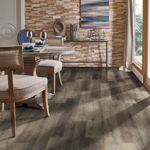 dining with vinyl plank flooring and stacked stone wall