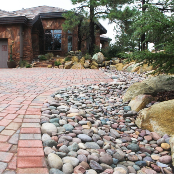 blue and red pebbles along bricked driveway