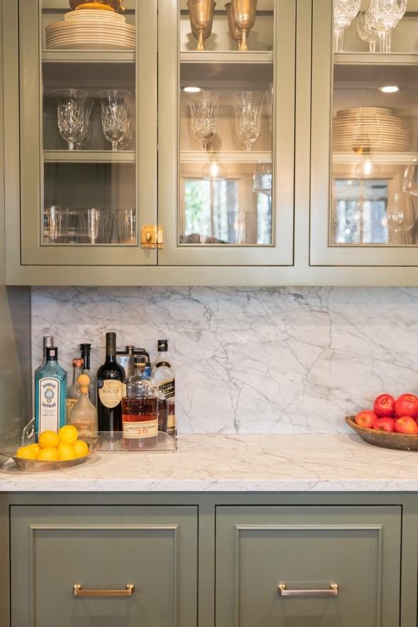 carrara white marble backsplash with green cabintry
