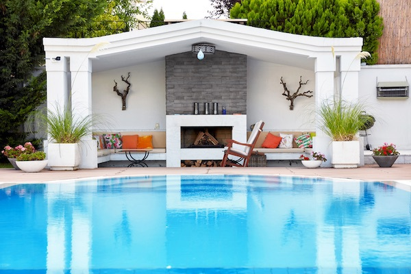 outdoor fireplace with stacked stone and pool