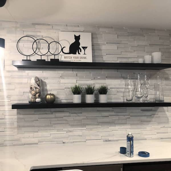 white stacked stone wall with shelving