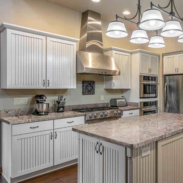 light+tan granite with swirl in white cabinet kitchen